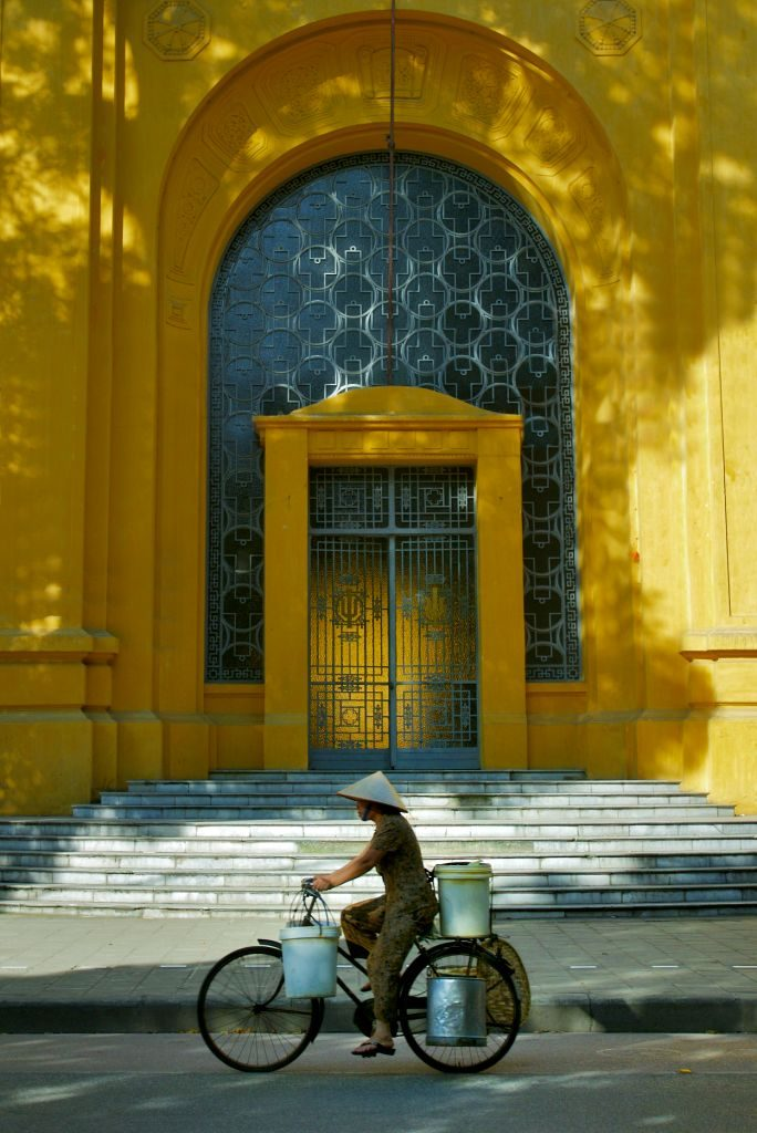 Lokal vietnameser med hatt og bøtter på sykkelstyret sykler forbi en massiv gul bygning med trapper foran